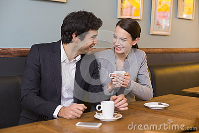 Cheerful couple flirting at coffee bar table