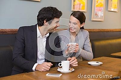 Cheerful couple flirting at coffee bar table