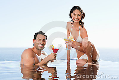 Cheerful couple having cocktails in the pool