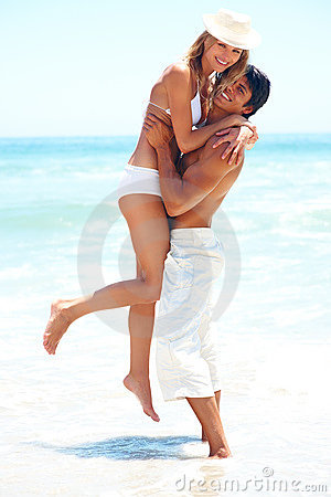 A cheerful couple having fun around on the beach