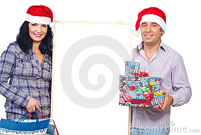 Cheerful couple hold gifts and blank banner