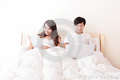 Cheerful couple using touch pad in bed