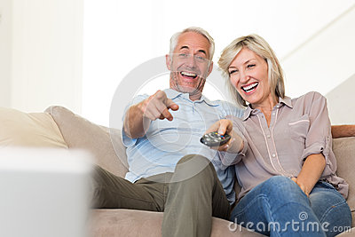 Cheerful couple watching tv at home