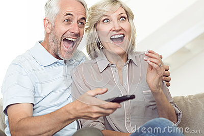 Cheerful couple watching tv on sofa