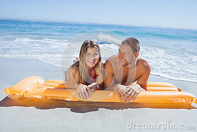 Cheerful cute couple in swimsuit lying on the beach