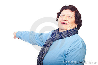 Cheerful elderly woman pointing to copy space