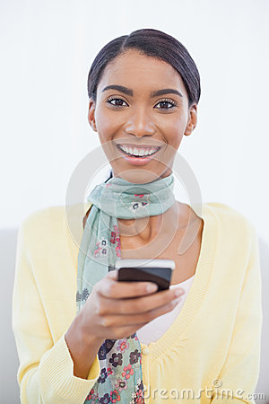 Cheerful elegant woman sitting on sofa text messaging