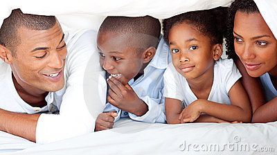 Cheerful family having fun lying down on bed