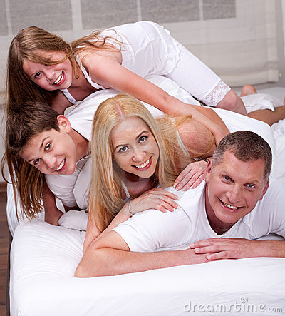 Cheerful family having fun together lying on a bed