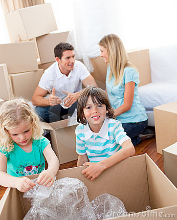 Cheerful Family Packing Boxes Stock Photos