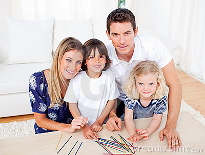 Cheerful family playing mikado in the living room
