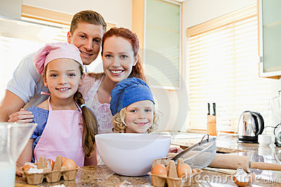 Cheerful family preparing dough