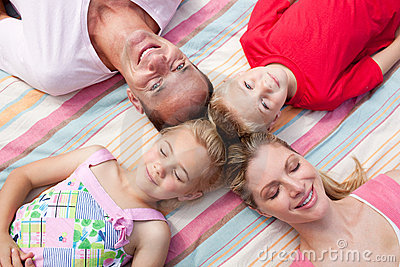 Cheerful family sleeping lying on the grass