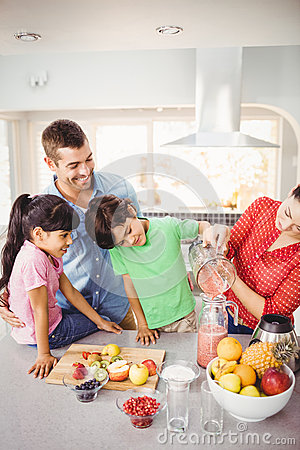 Free Cheerful Family With Mother Pouring Fruit Juice In Jug Stock Image - 67747581