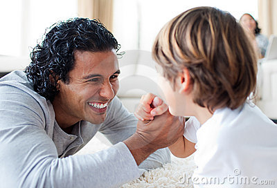 Cheerful father and his son arm wrestling
