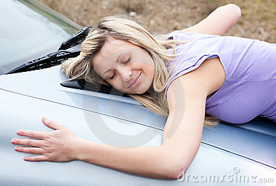 Cheerful female driver hugging her new car