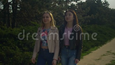 Cheerful female friends enjoying walk in spring park stock footage