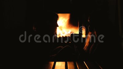 Cheerful female friends sitting at home in front of fireplace and talking. Teen girls have a chat by the cozy fire place. 1080 stock video footage