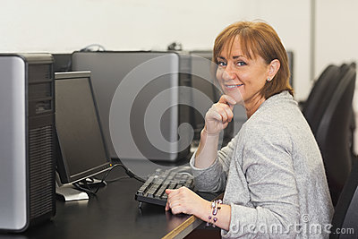 Cheerful female mature student sitting in computer class