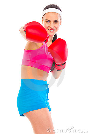 Cheerful fit young girl in boxing gloves punching