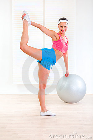 Cheerful fitness girl doing stretching exercises