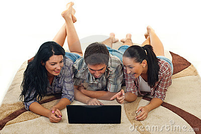 Cheerful friends on carpet using laptop