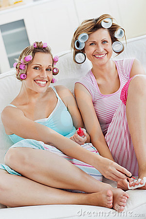 Cheerful friends with hair rollers doing pedicure