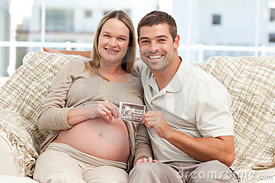 Cheerful future parents holding a sonogram