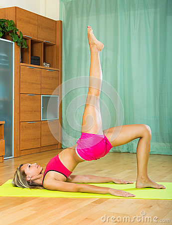 Cheerful girl doing yoga at home