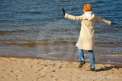 Cheerful girl walks on beach in solar autumn day