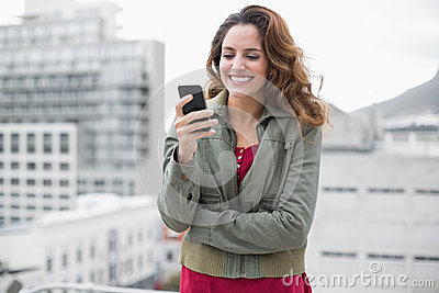 Cheerful gorgeous brunette in winter fashion holding smartphone