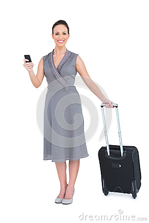 Cheerful gorgeous woman with her suitcase texting