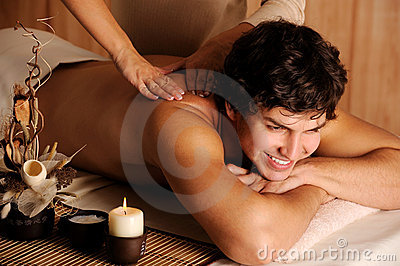 Cheerful guy getting massage and relaxation