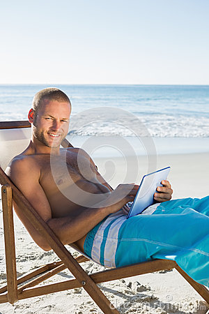 Cheerful handsome man using his tablet while sunbathing