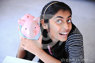 Cheerful Indian girl holding Piggybank
