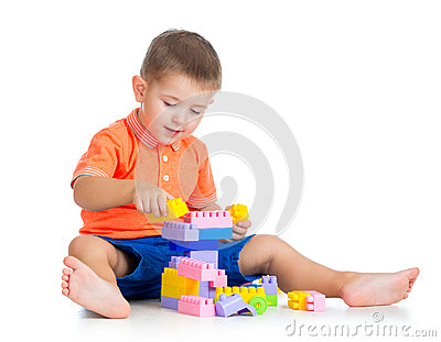 Cheerful kid boy playing with construction set over white back