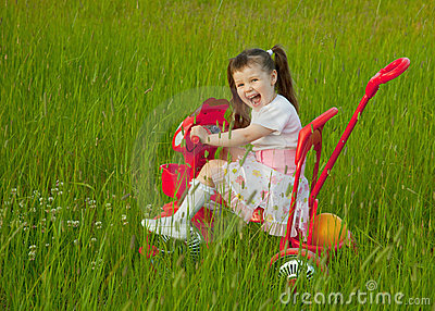 Cheerful little girl goes on a bicycle