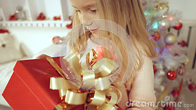 Cheerful little girl having fun with a gift near the Christmas tree Stock Photo