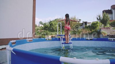 Cheerful little girl is having fun in the outdoors swimming pool. Slow Motion 240 fps. Child is jumping and playing in stock video footage