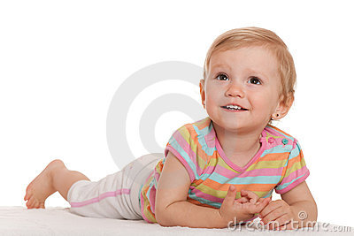 Cheerful little girl lying on the white looking up