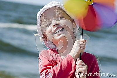 Cheerful little girl with pinwheel III