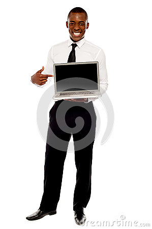 Cheerful male executive pointing at open laptop
