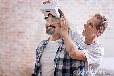 Cheerful male friends testing the virtual reality glasses Stock Photo