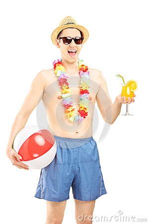 Cheerful male in swimming shorts, holding a beach ball and cockt