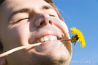 Cheerful man with dandelion portrait