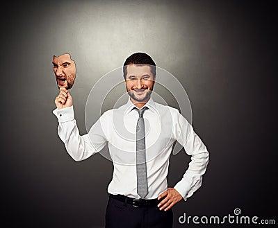 Cheerful man hiding behind angry mask