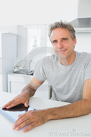 Cheerful man using tablet pc in kitchen
