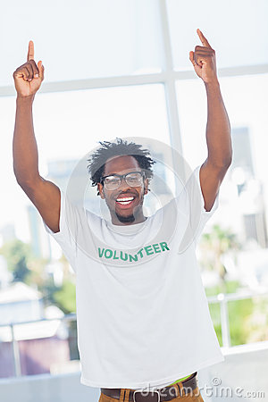 Cheerful man with volunteer tshirt raising his arms