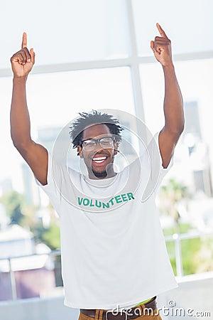 Cheerful man with volunteer tshirt raising his arms