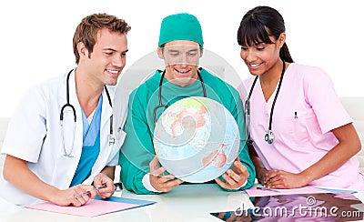 Cheerful medical team looking at terrestrial globe